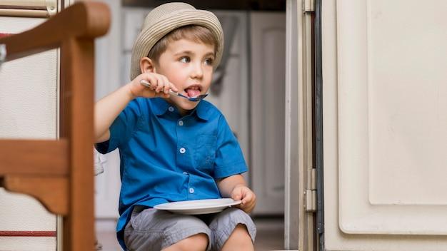 Mały chłopiec siedzi na przyczepie kempingowej podczas jedzenia
