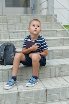 Mały chłopiec siedzi na schodach szkoły, trzymając zeszyty i patrząc w niebo