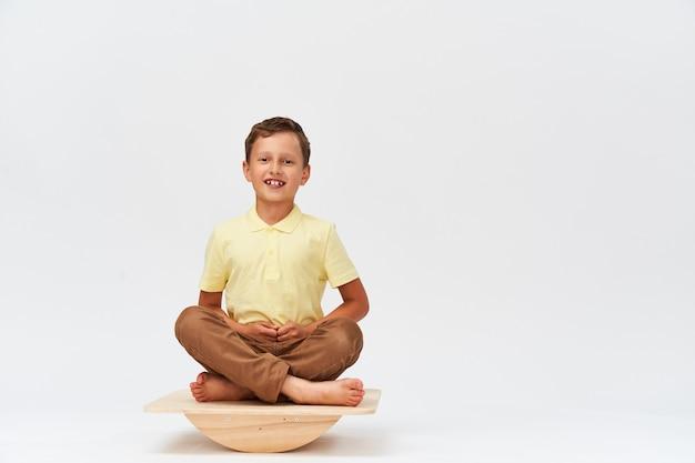 Mały chłopiec siedzi na specjalnym symulatorze do treningu aparatu przedsionkowego.