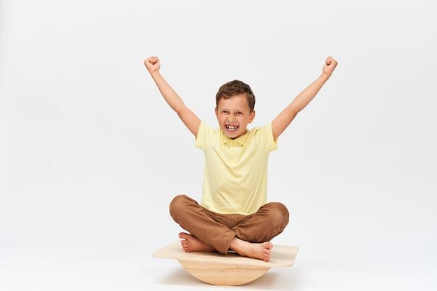 Mały chłopiec siedzi na specjalnym symulatorze do treningu aparatu przedsionkowego