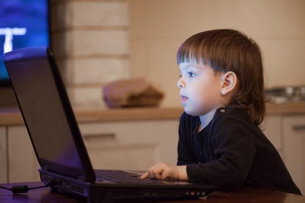 Mały chłopiec siedzi przy laptopie.