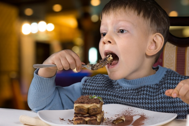Mały chłopiec siedzi przy stole i je duży kęs pysznego, świeżo upieczonego ciasta czekoladowego