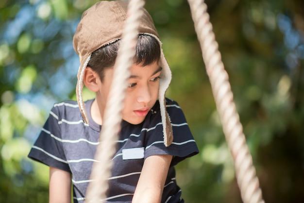 Mały chłopiec siedzi sam na huśtawce ze smutkiem