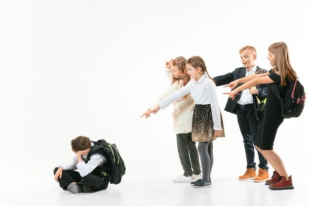 Mały chłopiec siedzi samotnie na podłodze i cierpi z powodu zastraszania, podczas gdy dzieci szydzą