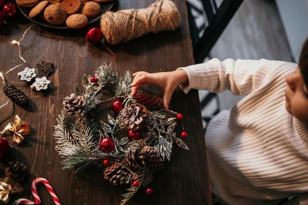 Mały chłopiec siedzi w kuchni i własnymi rękami robi świąteczny wieniec
