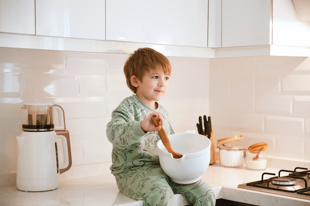 Mały chłopiec siedzi w kuchni, mieszając ciasto drewnianą łyżką.