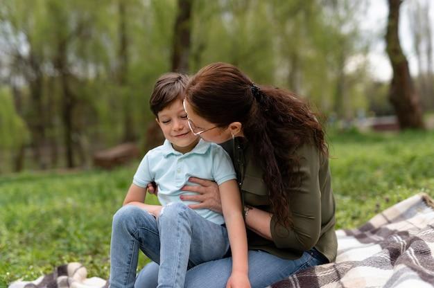 Mały chłopiec siedzi w parku z babcią