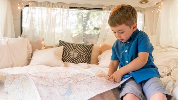 Mały chłopiec siedzi w przyczepie kempingowej i patrząc na mapę
