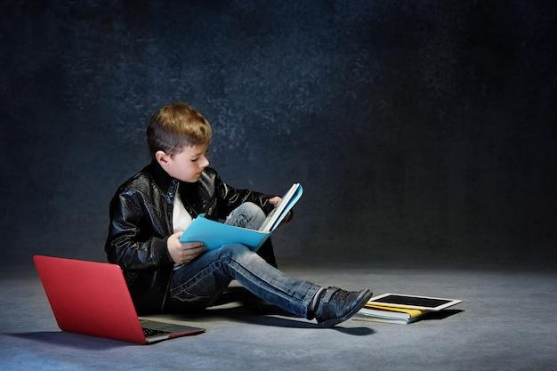 Mały chłopiec siedzi z gadżetami