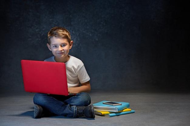 Mały chłopiec siedzi z laptopem