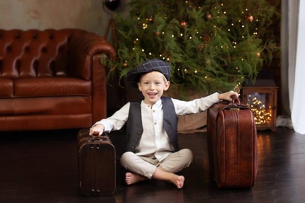 Mały chłopiec siedzieć na drewnianej podłodze w świątecznym salonie