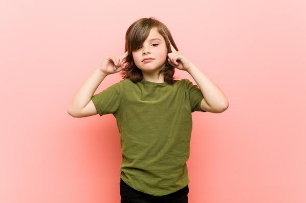 Mały chłopiec skupił się na zadaniu, trzymając palce wskazujące głową.