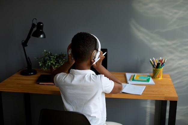 Mały chłopiec słucha swojego nauczyciela przez słuchawki