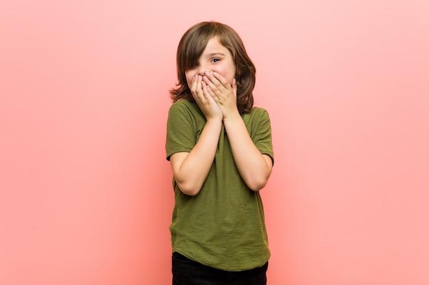Mały chłopiec śmieje się z czegoś, zasłaniając usta dłońmi.