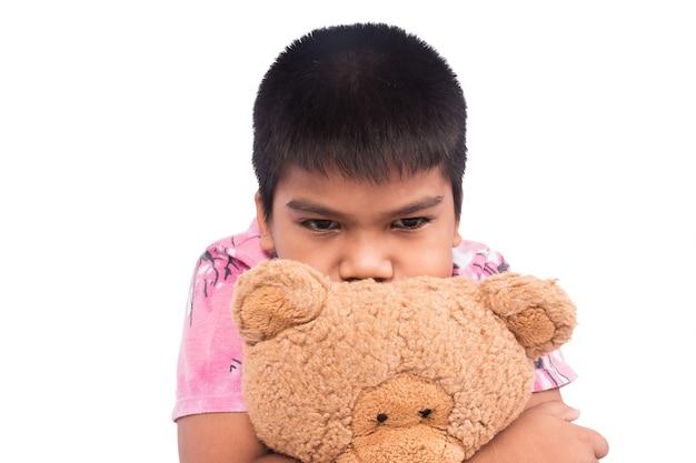 Mały chłopiec smutny z brązowym misiem