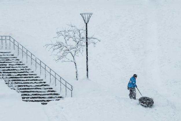 Mały chłopiec snowtubing podczas opadów śniegu