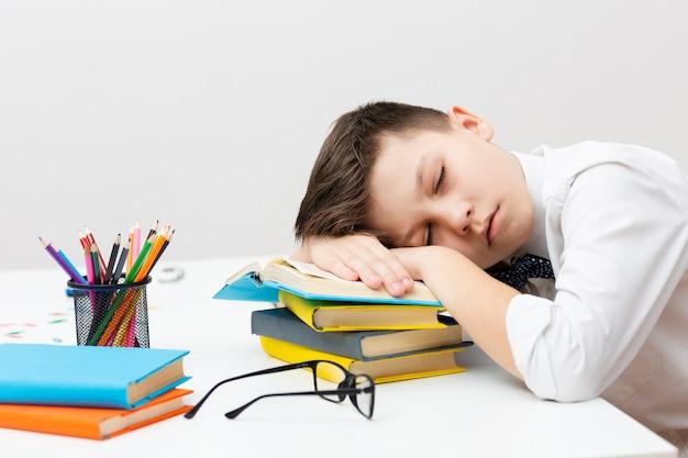 Mały chłopiec śpi na stosie książek