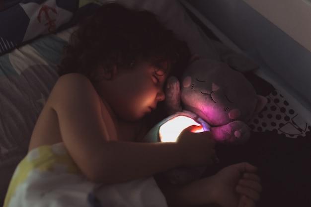 Mały chłopiec śpi nonszalancko w przytuleniu z zabawką w nocy
