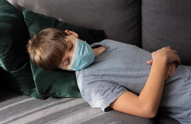 Mały chłopiec śpi w masce medycznej