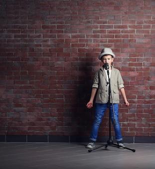 Mały chłopiec śpiewa z mikrofonem na tle ceglanego muru