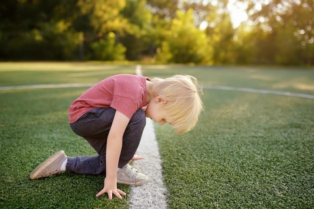 Mały chłopiec sportowiec przygotowuje się do uruchomienia odległość na stadionie szkolnym.