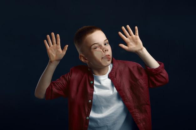 Mały chłopiec sprawia, że twarz opierając się o szybę w studio. szczęśliwe dzieciństwo, dzieci, zabawy, zabawne dziecko na białym tle na ciemnym tle, emocje dziecka