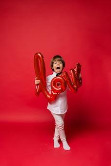 Mały chłopiec stoi i trzyma czerwony balon miłości na czerwonym tle z miejscem na tekst
