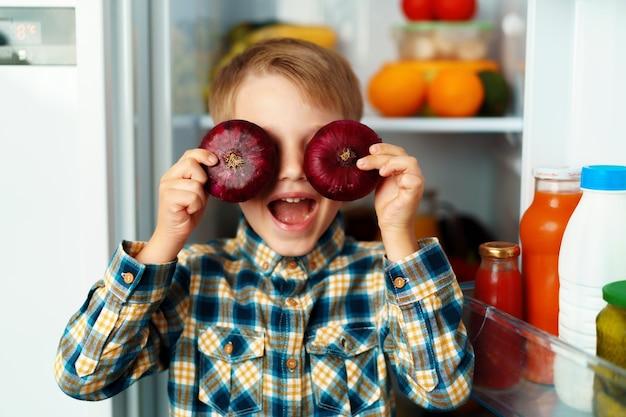 Mały chłopiec stoi przed otwartą lodówką i wybiera jedzenie