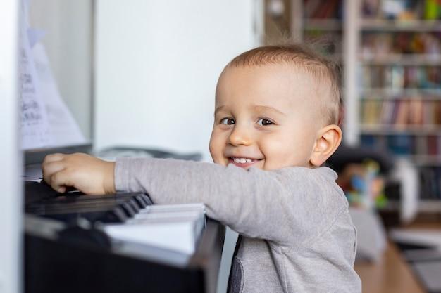 Mały chłopiec stoi przy pianinie i uśmiecha się. chłopczyk chce grać na pianinie w domu
