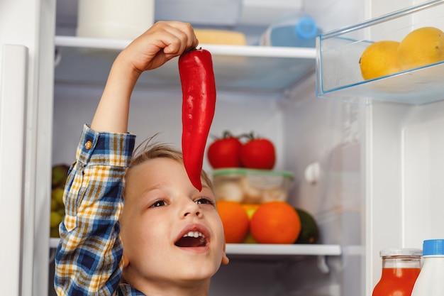 Mały chłopiec stojący przy otwartej lodówce