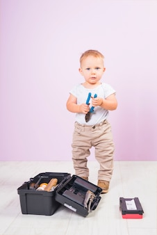 Mały chłopiec stojący z szczypce