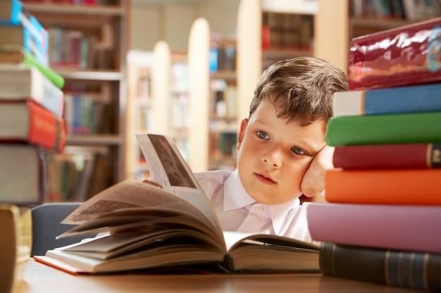 Mały chłopiec studiuje w bibliotece