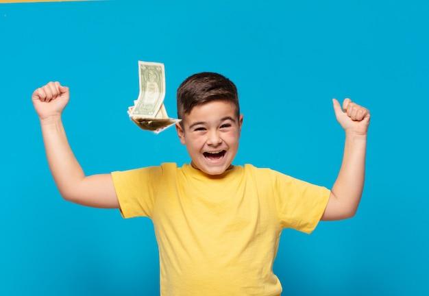Mały chłopiec świętuje zwycięstwo i banknoty dolarowe