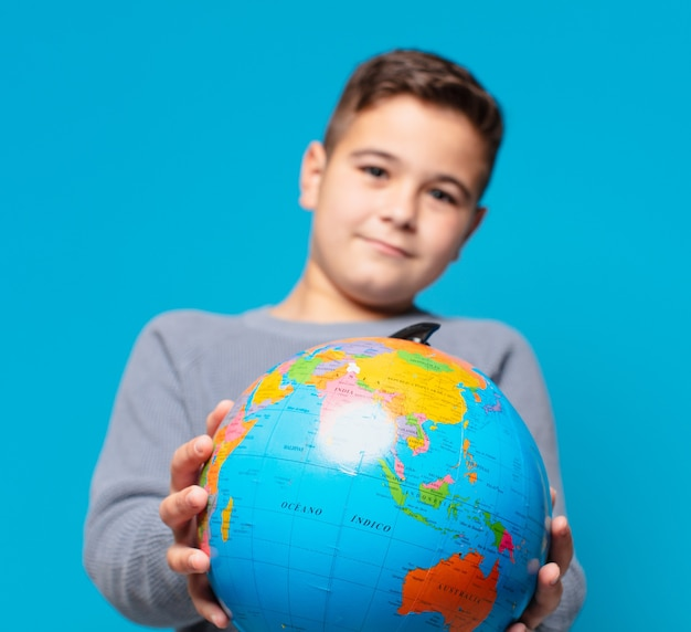 Mały chłopiec szczęśliwy wyraz i trzymający model mapy świata