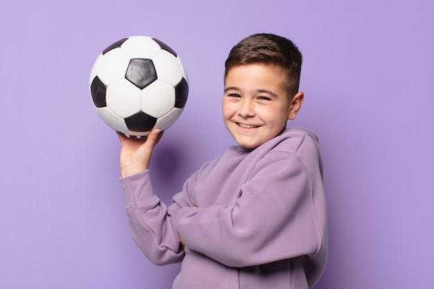 Mały chłopiec szczęśliwy wyraz i trzymający piłkę nożną