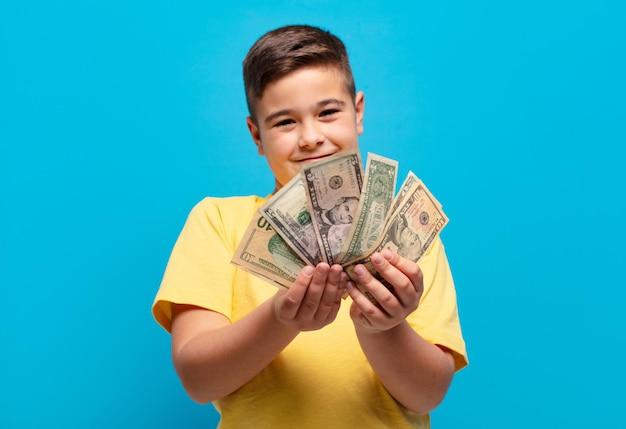 Mały chłopiec szczęśliwy wyraz z banknotami dolarowymi