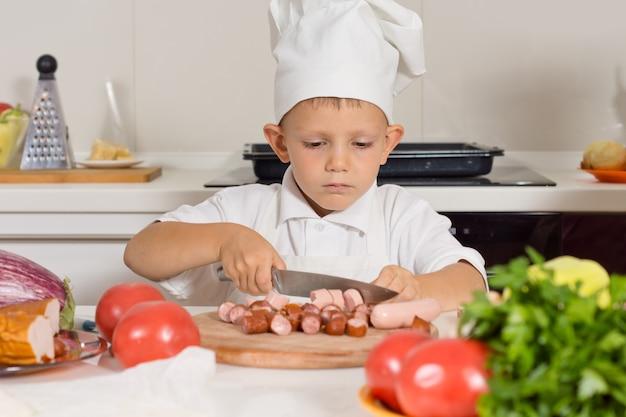 Mały chłopiec szkolący się na szefa kuchni