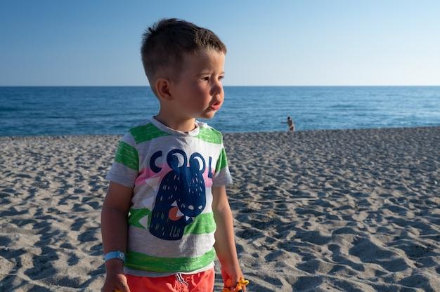 Mały chłopiec szuka swojej mamy na plaży.