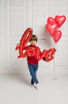 Mały chłopiec trzyma balon miłości na białym tle z balonami sercami