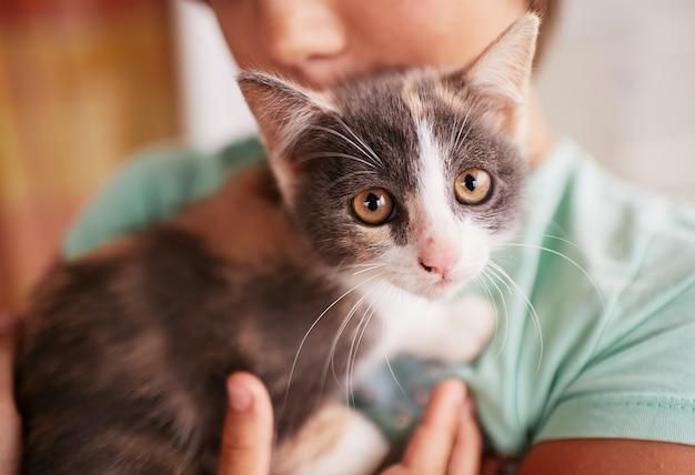 Mały chłopiec trzyma czarno-białe kitty na ramieniu