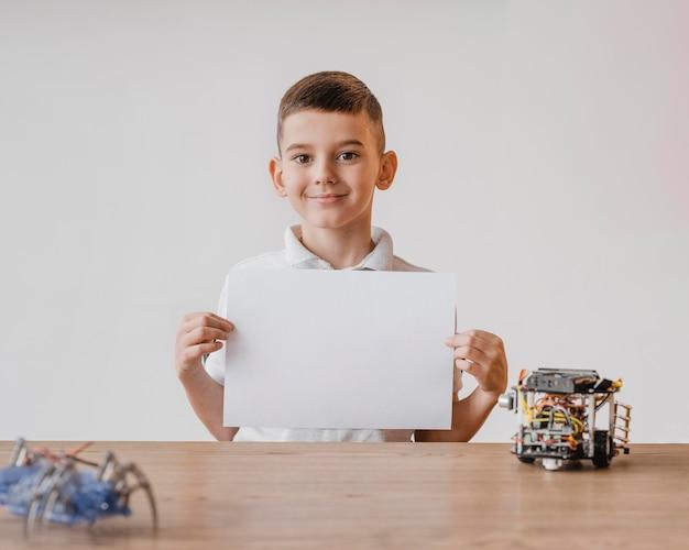 Mały chłopiec trzyma czysty papier