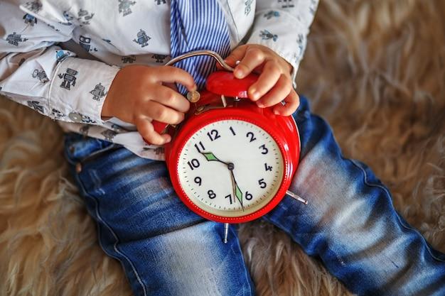 Mały chłopiec trzyma duży czerwony zegar czeka