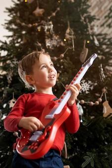 Mały chłopiec trzyma gitarę obok drzewa