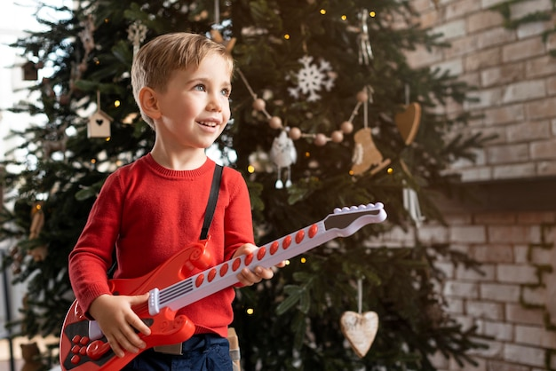 Mały chłopiec trzyma gitarę z miejsca na kopię
