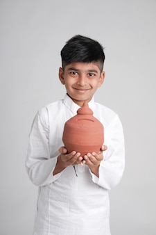 Mały chłopiec trzyma glinianą skarbonkę