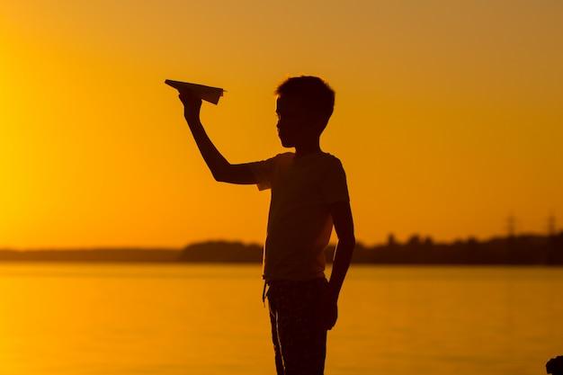 Mały chłopiec trzyma origami o zachodzie słońca wieczorem. bawi się samolotem, który sam zbliżył się do rzeki