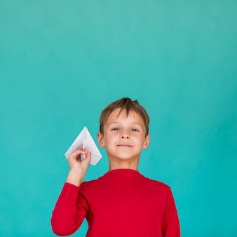 Mały chłopiec trzyma papierowy samolot