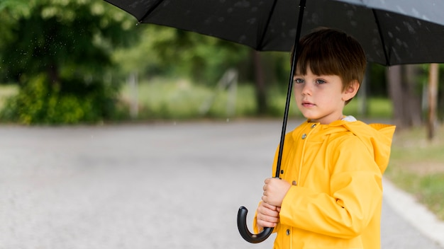 Mały chłopiec trzyma parasol z miejsca na kopię