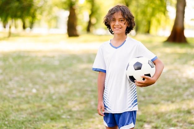 Mały chłopiec trzyma piłkę nożną z miejsca na kopię