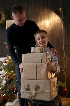 Mały chłopiec trzyma prezenty świąteczne
